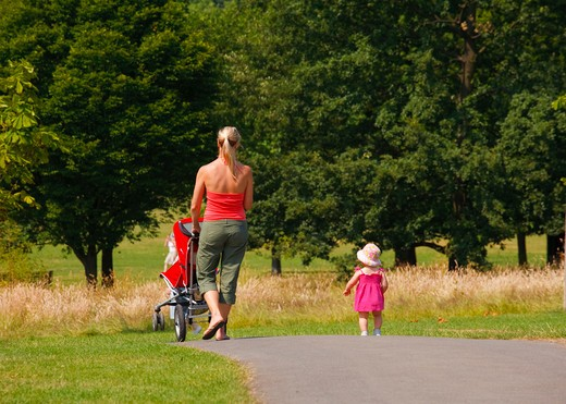 Stock Photo: 4282-20655 England, London, Regent's Park. A mother walking with her young daughter and pushing a pushchair in Regent's Park.