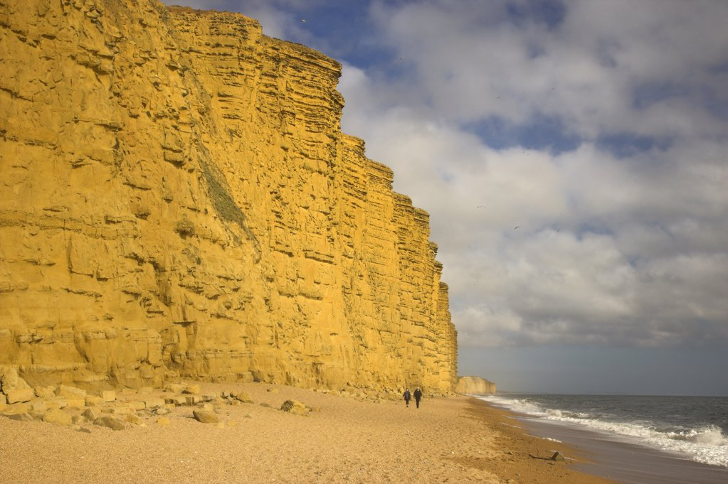 Stock Photo: 4282-20714 England, Dorset, West Bay. People walking along the beach below the sandstone East Cliff of West Bay on the Jurassic Coast in Dorset.