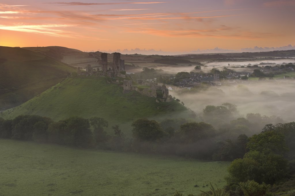 England, Dorset, Corfe Castle. Corfe Castle surrounded by low lying mist at dawn. : Stock Photo