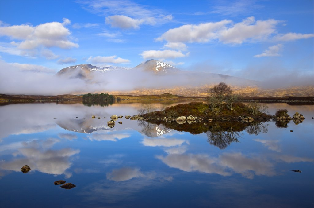 Stock Photo: 4282-20910 Scotland, Argyll and Bute, Rannoch Moor. Rare combination of clouds, mirror reflections, and mist slowly clearing the mountains by Lochan na h-Achlaise on Rannoch Moor.