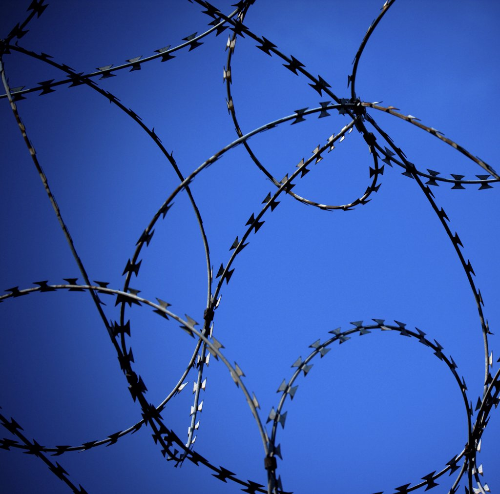 England, North Yorkshire, York. A close up of rings of barbed wire against a blue sky in York. : Stock Photo