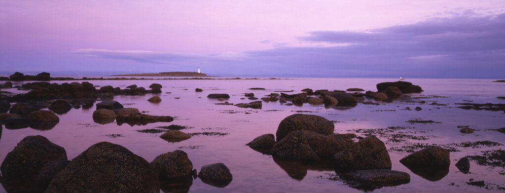 Stock Photo: 4282-2126 Scotland, North Ayrshire, Isle of Arran. Dusk falls on the lighthouse on Pladda just off the southern shore of Arran. In the 2001 census the Isle of Arran had a resident population of 5,058.