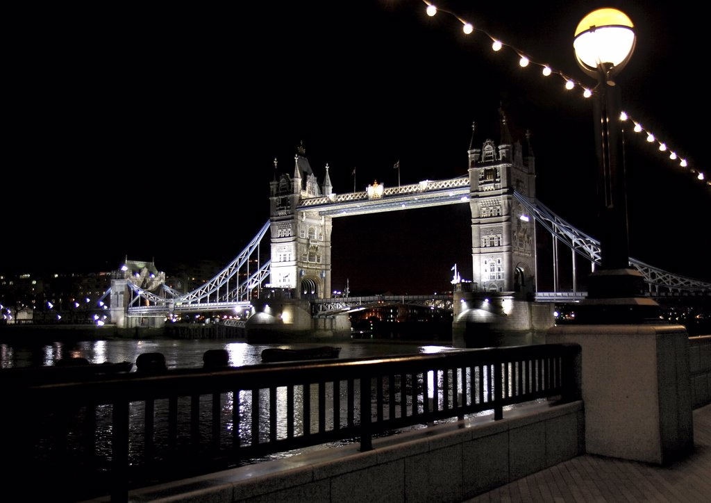 Stock Photo: 4282-21279 England, London, Tower Bridge. A view over the Thames to an illuminated Tower Bridge at night.