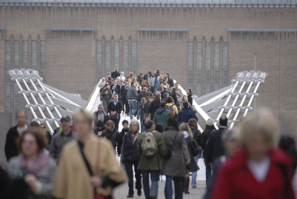 Stock Photo: 4282-21468 England, London, Millenium Bridge. People crossing the Millennium Bridge. The bridge is a 330m steel bridge linking the City of London at St. Paul's Cathedral with the Tate Modern Gallery at Bankside.