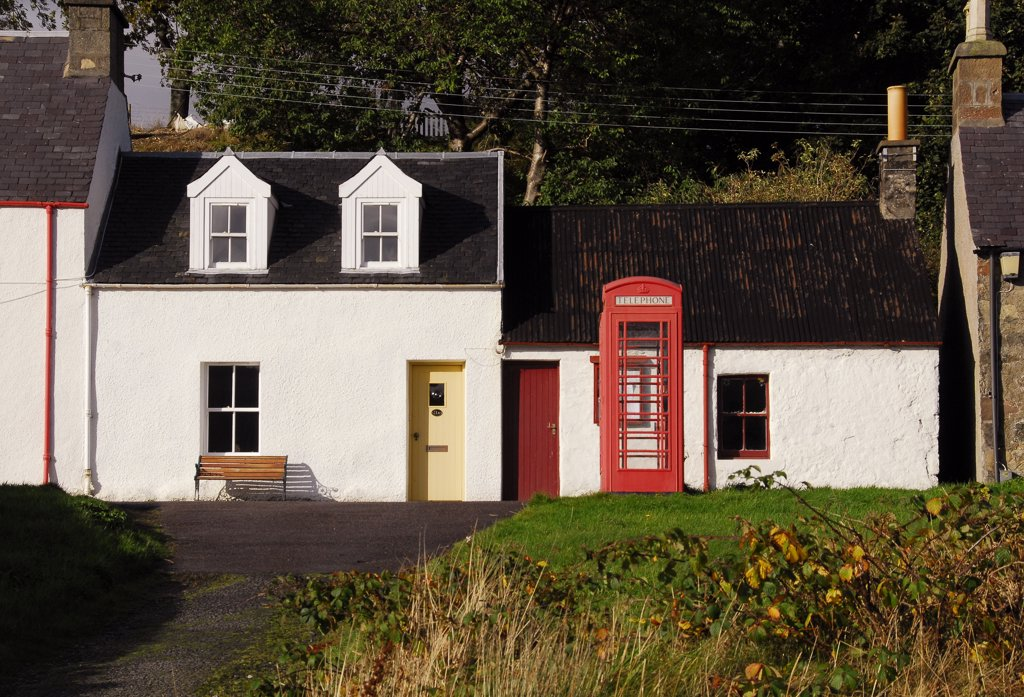 Stock Photo: 4282-21728 Scotland, Highland, Kyle of Lochalsh. Red telephone box with cottages in the village of Plockton. The village has National Trust conservation status.