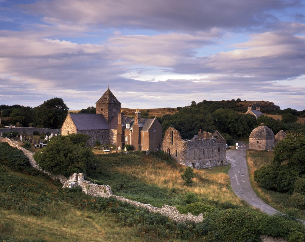 Stock Photo: 4282-21769 Wales, Anglesey, Beaumaris. Fading sunlight illuminates the remains on Penmon Priory and Priory church which serves as the parish church today.