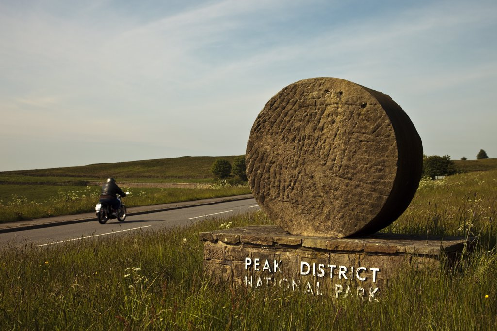 Stock Photo: 4282-22604 England, Derbyshire, Curbar. A lone motorcyclist rides into the Peak District National Park past one of the stone signs that marks Britain's first national park, established in 1951.