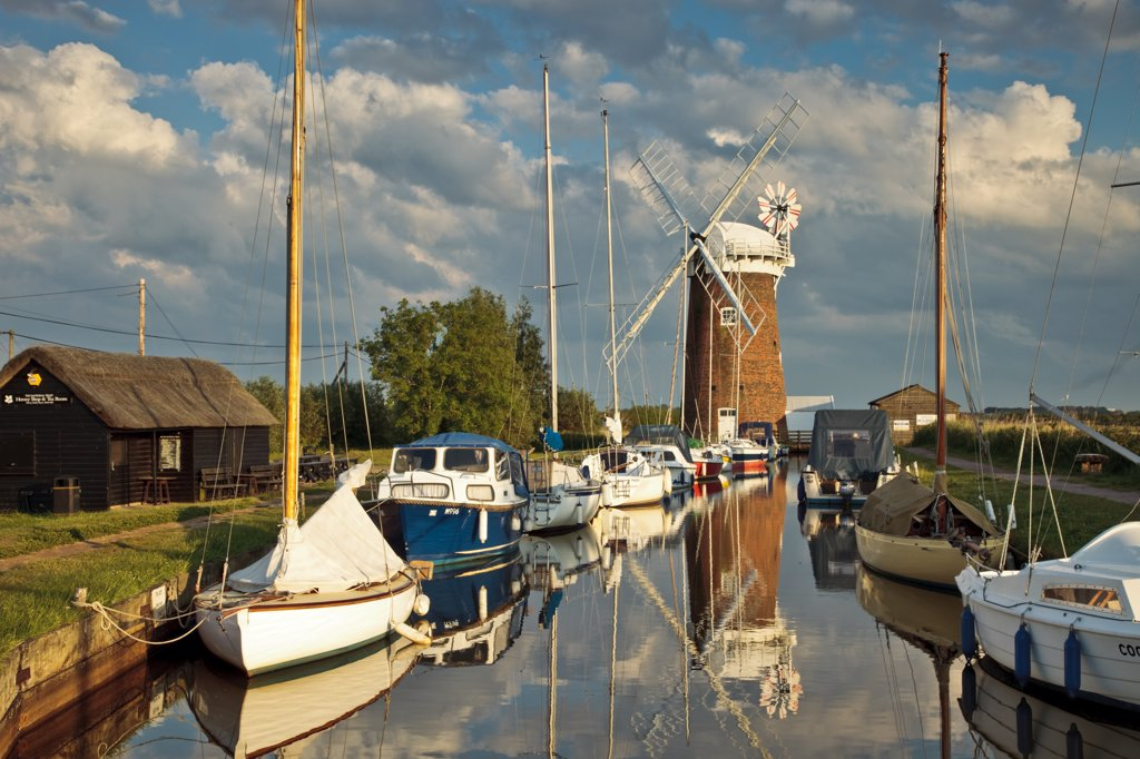 Stock Photo: 4282-22606 England, Norfolk, Horsey. Relections of Horsey Windpump and boats in Horsey Mere on the Norfolk Broads.