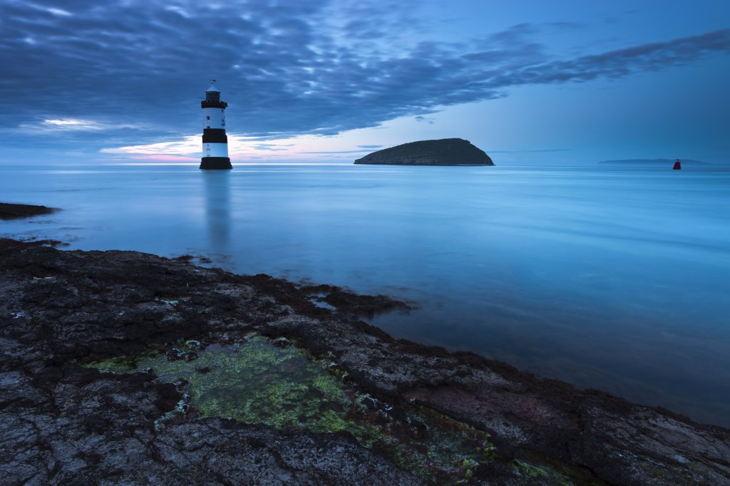 Wales, Anglesey, Penmon. Penmon lighthouse and Puffin Island at Penmon Point on the Isle of Anglesey. : Stock Photo