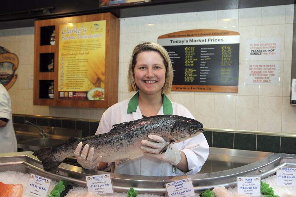 Stock Photo: 4282-22811 Republic of Ireland, County Mayo, Ballina. A wild Salmon held by a shop assistant in Clarke's Seafood Delicatessen. Clarke's has supplied salmon to the Vatican.