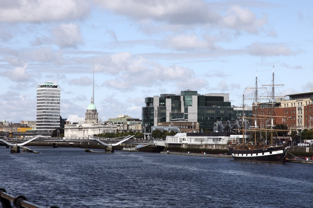 Stock Photo: 4282-22826 Republic of Ireland, Dublin City, Dublin. View along the River Liffey towards Custom House Quay from the South Quays featuring Liberty Hall, Customs House, the chq Building, AIB Trade Centre, Sean O'Casey Bridge and the replica Famine Ship Jeanie Johnston.