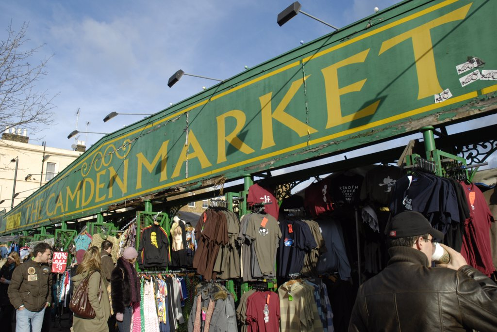 England, London, Camden Town. A view of the Camden Market sign above clothing stalls. : Stock Photo