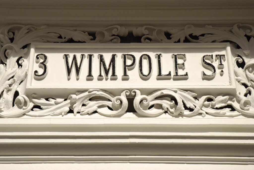 England, London, Westminster. A close up of an old ornate white stone sign on Wimpole Street. : Stock Photo
