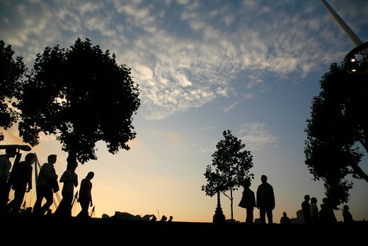 England, London, South Bank. Pedestrians silhouetted against the setting sun on Queens Walk outside Royal Festival Hall on the South Bank. : Stock Photo