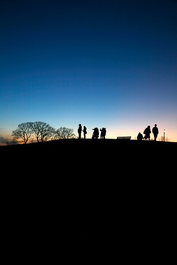 England, London, Primrose Hill. Figures silhouetted at sunset on top of Primrose Hill. : Stock Photo