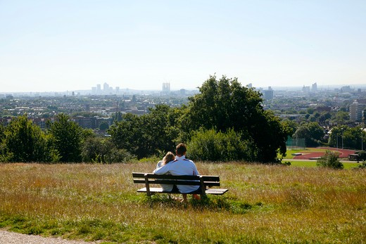 England, London, Parliament Hill. A couple enjoy the view of the City of London skyline from the top of Parliament Hill on Hampstead Heath. : Stock Photo