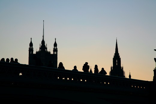 England, London, Westminster. Pedestrians on Westminster Bridge silhouetted against the Houses of Parliament. : Stock Photo