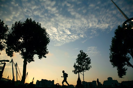 Stock Photo: 4282-24967 England, London, South Bank. A silhouetted runner on the Queen's Walk outside Royal Festival Hall on the South Bank.