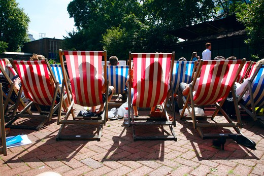 England, London, Charing Cross. People sunbathing on deckchairs in Victoria Embankment Gardens. : Stock Photo