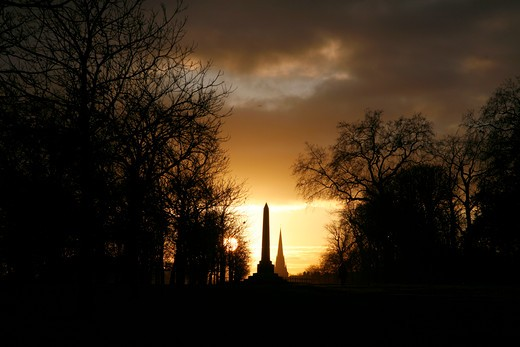 England, London, Kensington Gardens. The sun setting behind the Speke Monument and St Mary Abbot's church in Kensington Gardens. : Stock Photo