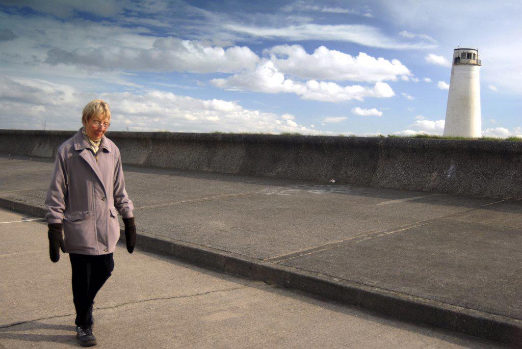 Stock Photo: 4282-25282 England, Merseyside, Wallassey. A woman walking by the sea.