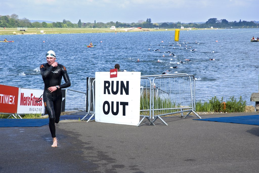 Stock Photo: 4282-26136 England, Berkshire, Windsor. A triathlete leaving the water and running towards the transition area at Eton Dorney, the venue for Rowing, Paralympic Rowing and Canoe Sprint events during the London 2012 Games.