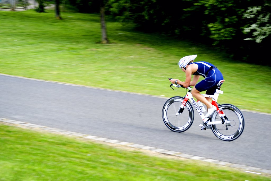 England, Berkshire, Windsor. A triathlete cycling out on the course during a triathlon event at Eton Dorney, an Olympic venue for the London 2012 Games. : Stock Photo