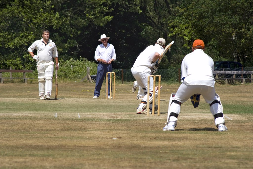 England, Surrey, Headley. Cricket on the village green at Headley. : Stock Photo