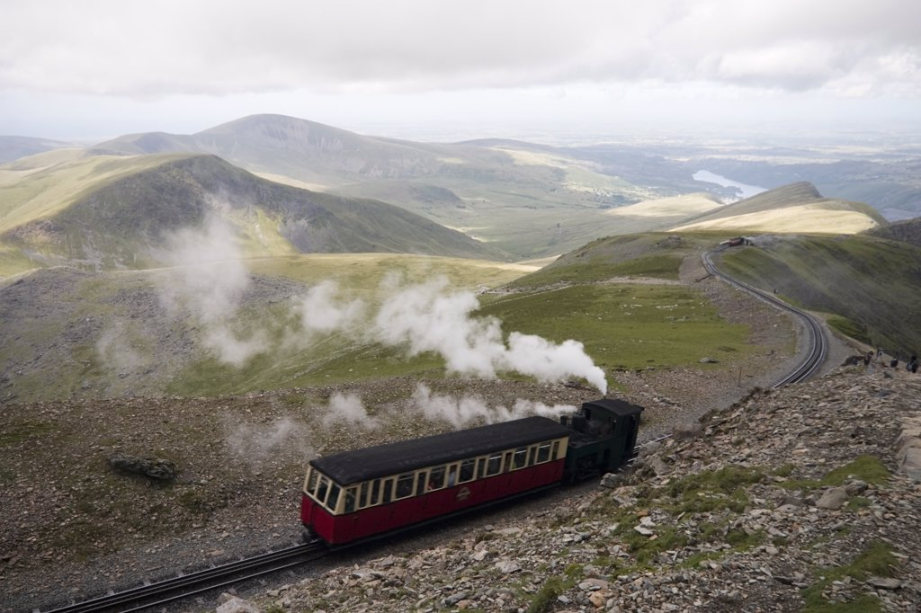 Stock Photo: 4282-26426 Wales, Gwynedd, Snowdon Mountain Railway. A Snowdon mountain railway steam train pushing a carriage up a mountain on Snowdon. It is over 100 years old and is the only public rack railway in the British Isles.