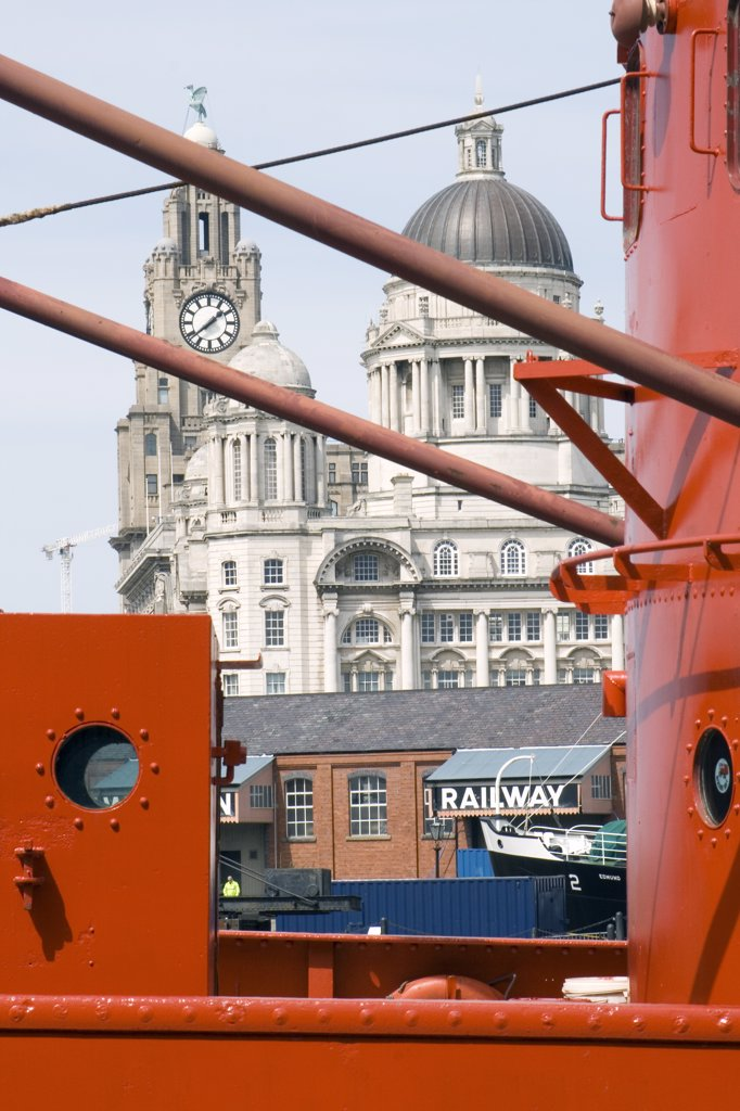 Stock Photo: 4282-26492 England, Merseyside, Liverpool. Bright orange boat moored in Liverpool docks with the Liver Building in the distance.