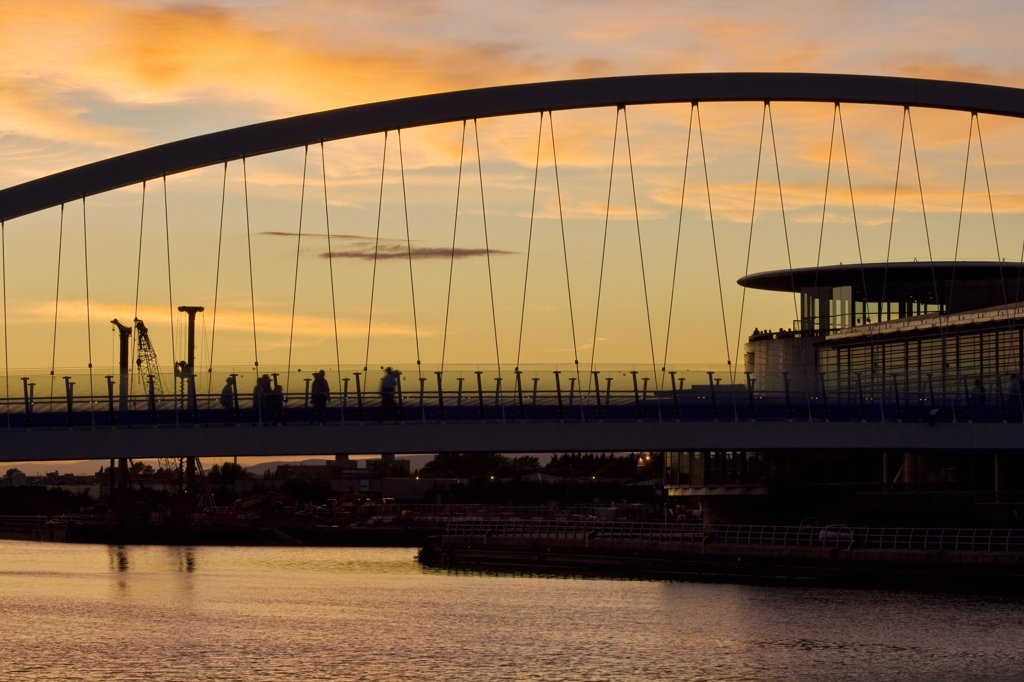 England, Greater Manchester, Salford Quays. Outline of Salford Quays Millennium Bridge at sunset. : Stock Photo