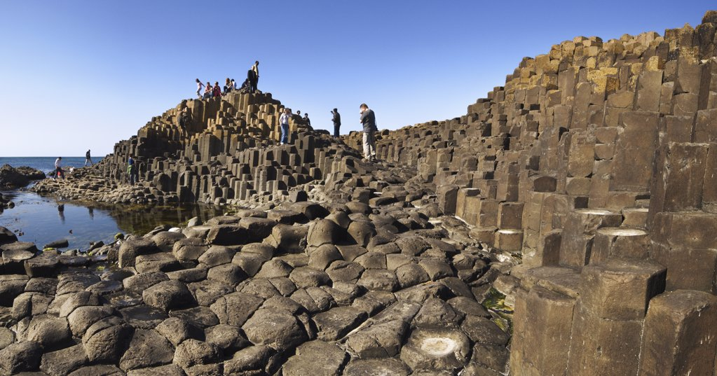 Stock Photo: 4282-27635 Northern Ireland, County Antrim, Giants Causeway. Tourists exploring the interlocking basalt columns of the Giants Causeway,  a World Heritage Site and National Nature Reserve.