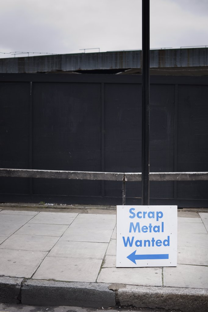 England, London, Hackney. Scrap Metal Wanted sign leaning against a lamp post. : Stock Photo