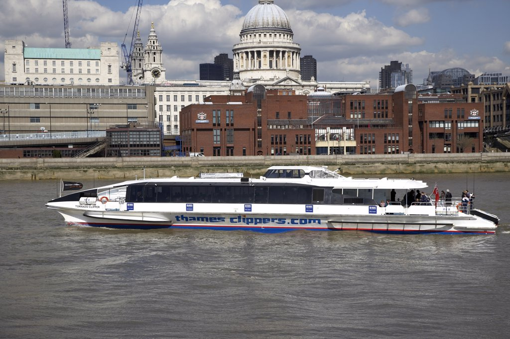 England, London, South Bank. A view across the water to a Thames Clipper going past St Pauls. : Stock Photo