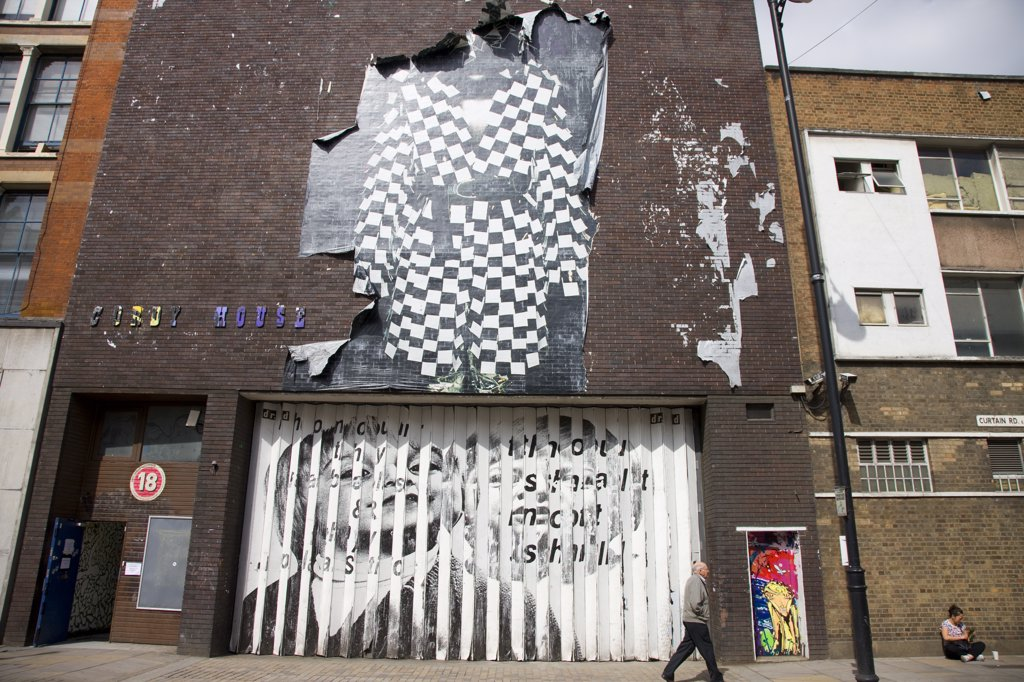 Stock Photo: 4282-28331 England, London, Shoreditch. A man walking past the front of Cordy House (a venue with 20,000 square feet of event space) displaying Graffiti and a large torn poster in Curtain Road.