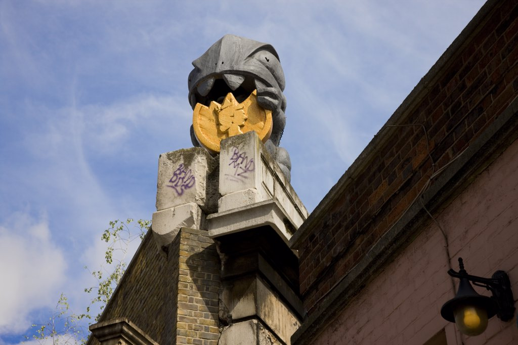 Stock Photo: 4282-28332 England, London, Great Eastern Street. Post Modernist money munching street sculpture on top of a building in Great Eastern Street.