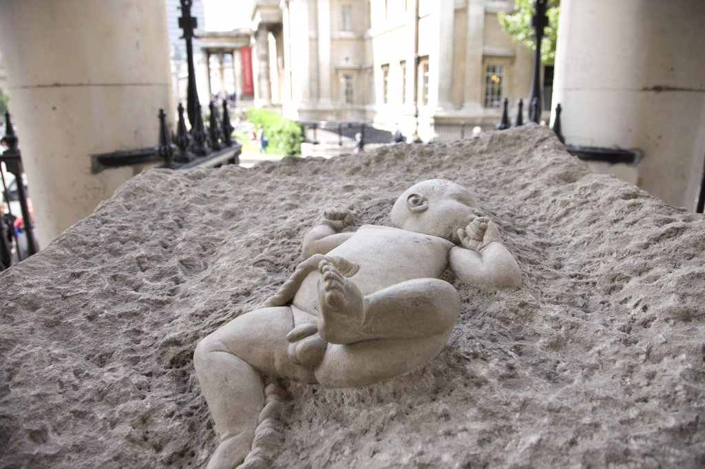 Stock Photo: 4282-28355 England, London, Trafalgar Square. A sculpture of a new born baby in a block of concrete outside St Martin in the Fields near Trafalgar Square.