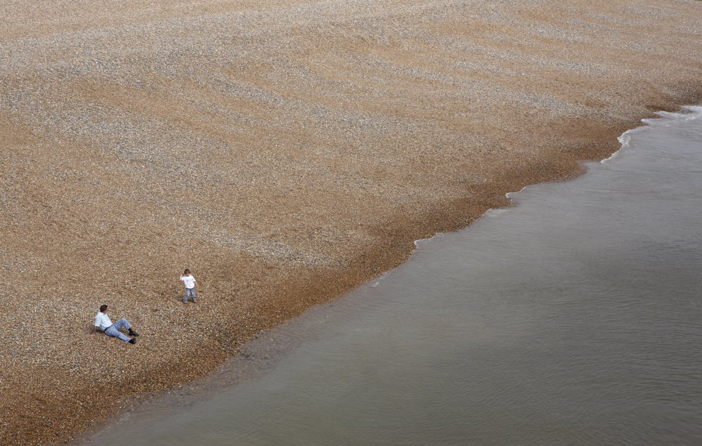 Stock Photo: 4282-28491 England, East Sussex, Brighton. A father and son on a deserted pebble beach.