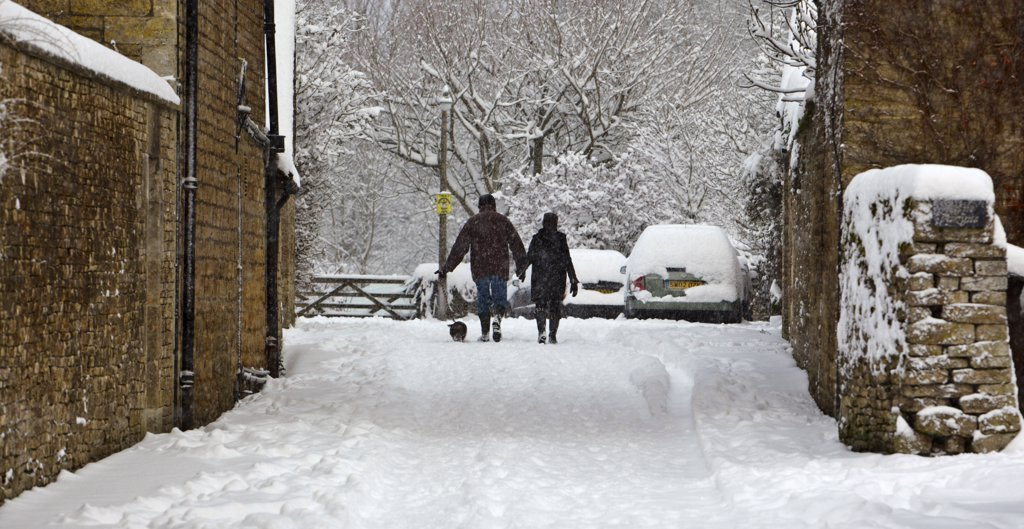 England, Gloucestershire, South Cerney. A couple walking a small dog through heavy snow in a Cotswold village. : Stock Photo