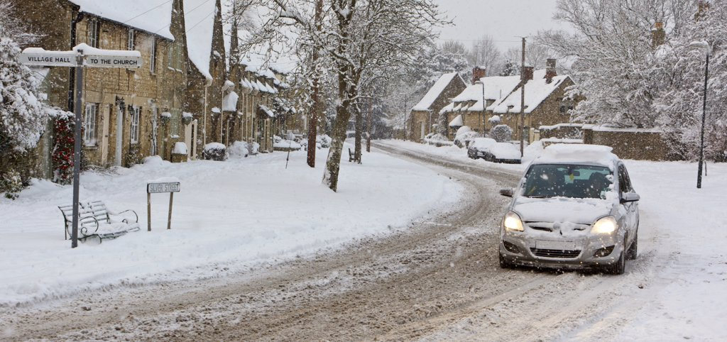 Stock Photo: 4282-28688 England, Gloucestershire, South Cerney. A car struggling through falling snow on Silver Street in the Cotswolds village of South Cerney.