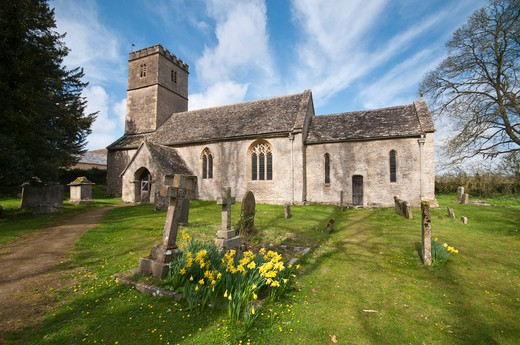 England, Gloucestershire, Coln Rogers. The Parish Church of St Andrew with daffodils in the churchyard in the Cotswold village of Coln Rogers. : Stock Photo