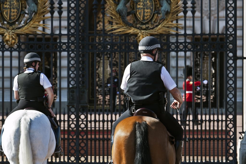 England, London, Buckingham Palace. Mounted police officers and a Queen's Guard on duty outside Buckingham Palace. : Stock Photo