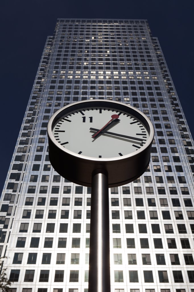 England, London, Canary Wharf. One of 'Six Public Clocks', a sculpture by Konstantin Grcic in Nash Court with One Canada Square, the second tallest building in the UK, in the background. : Stock Photo