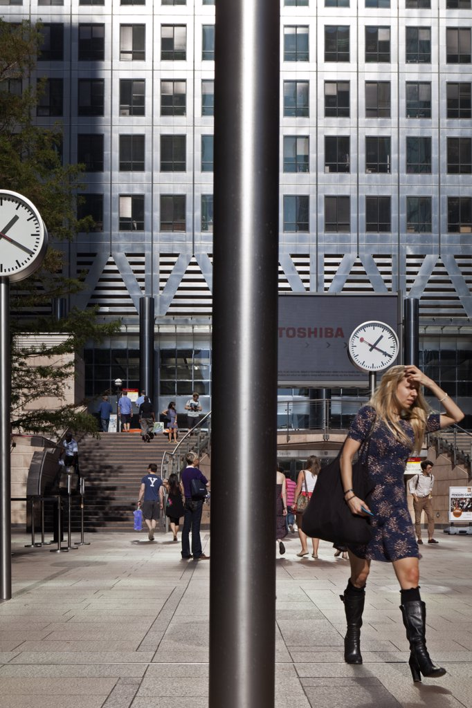 Stock Photo: 4282-29029 England, London, Canary Wharf. 'Six Public Clocks', a sculpture by Konstantin Grcic and office workers in Nash Court outside One Canada Square, the second tallest building in the UK.