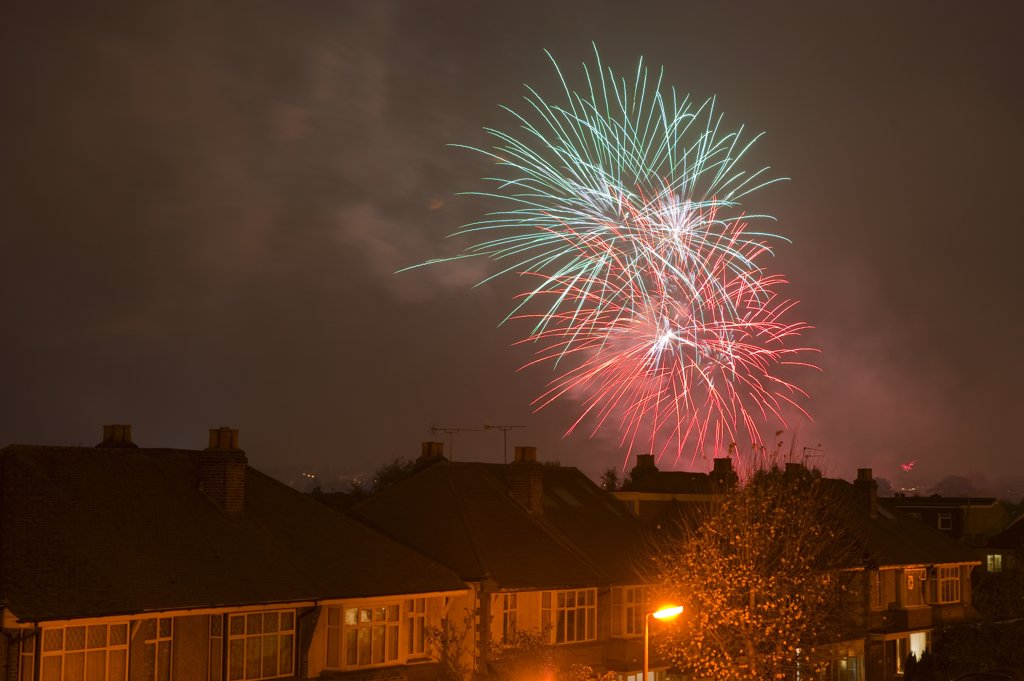 England, London. Evening firework display above houses in the suburbs of London on Guy Fawkes night (bonfire night), celebrated annually on the 5th November. : Stock Photo