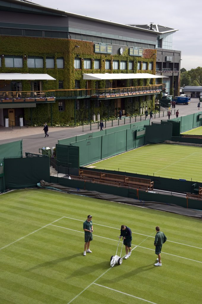 England, London, Wimbledon. Groundsmen painting the white lines on court 4 during the 2011 Wimbledon Tennis Championships. : Stock Photo