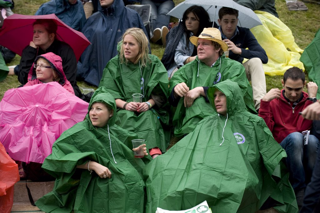 England, London, Wimbledon. Fans sitting on Aorangi Terrace (Henman Hill) wearing rain capes during a rain delay at the 2011 Wimbledon Tennis Championships. : Stock Photo