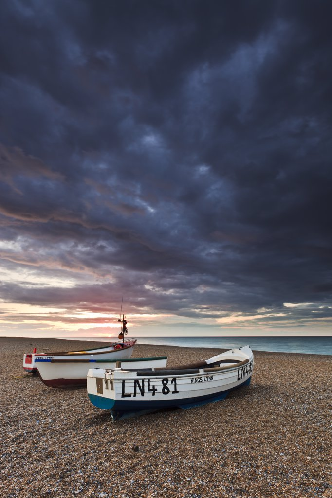 England, Norfolk, Cley next the Sea. Three small fishing boats on the shingle beach of Cley next the Sea on the North Norfolk coast. : Stock Photo