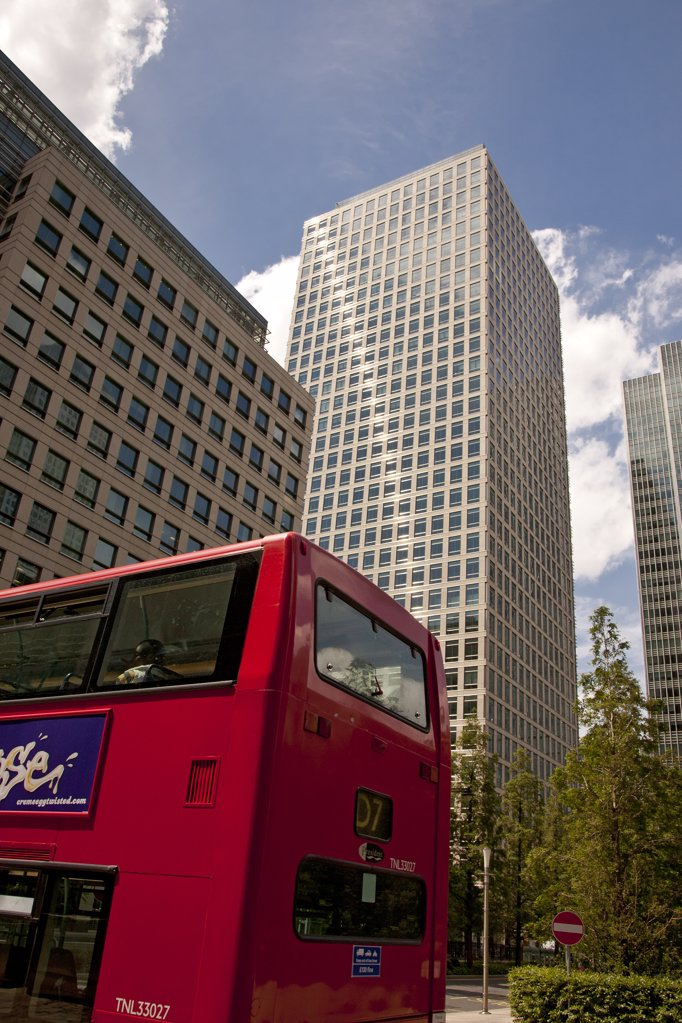 Stock Photo: 4282-29567 England, London, Canary Wharf. Red London double decker bus travelling through the new financial district at Canary Wharf.
