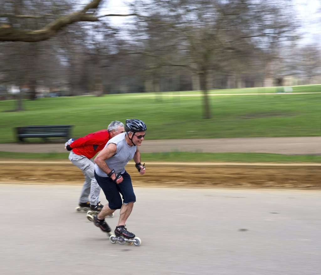 England, London, Hyde Park. Two men skating at speed through Hyde Park. : Stock Photo
